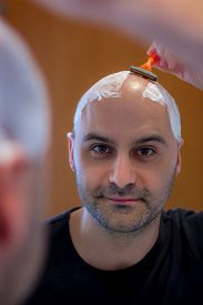 picture of shaved head  - man who shaves his head with a razor reflected in the mirror - JPG