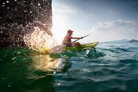 pic of kayak  - Young lady paddling hard the sea kayak with lots of splashes - JPG