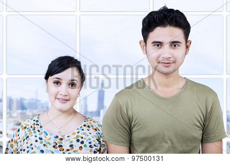 Happy Couple Looking At Camera In Apartment