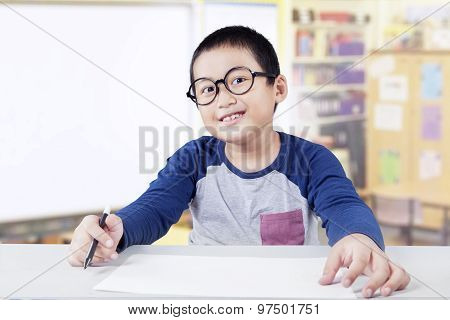 Schoolboy Holds Marker And Empty Paper In Class