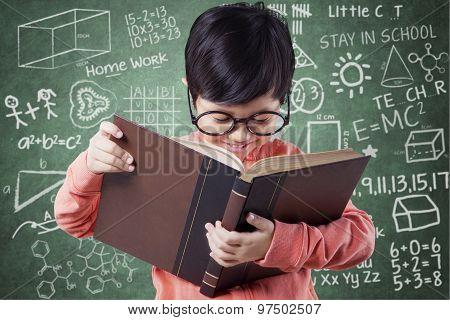 Sweet Girl Learn With Book Near Blackboard
