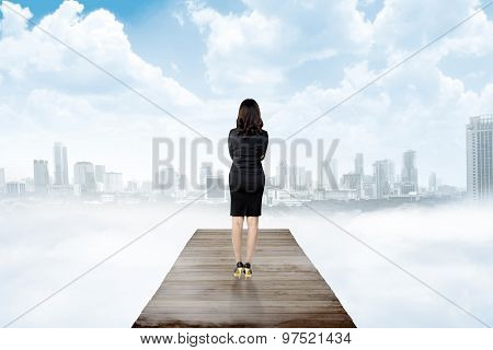 Backview Of Business Woman Looking The City From Wooden Pier