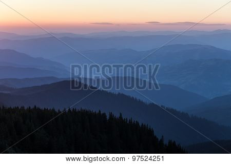 Distant Mountain Range And Thin Layer Of Clouds On The Valleys