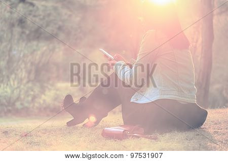 Pretty young woman sit in the park with cell phone