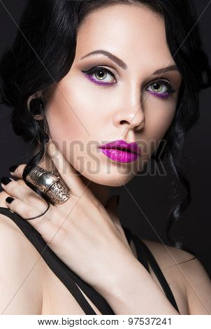 Beautiful Girl in the Gothic style with leather accessories and bright makeup.