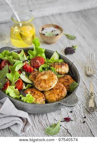 Chicken Cutlets And Fresh Vegetable Salad In A Pan On A Light Wooden Background