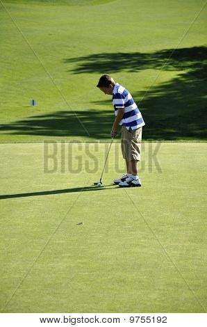 Young Boy Putting On Golf Course