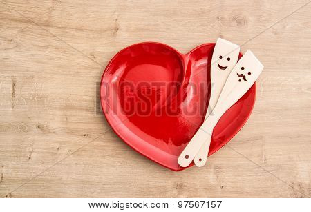 Wooden Kitchen Utensils On Red Hearth Plate. Funny Food