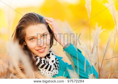Beautiful brunette girl sitting in autumn grass with smilling face. Concept of happiness and joy