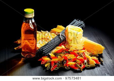 Raw pasta and oil on black table, italian cuisine concept