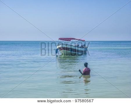 Black Man And A Boat On Caribbean Sea