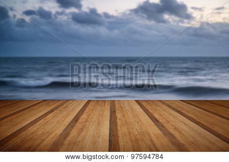 Stunning Vibrant Winter Sunset Over Long Exposure Receding Waves With Wooden Planks Floor