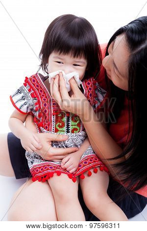 Asian Mother Wipes Snot Her Daughter On White Background