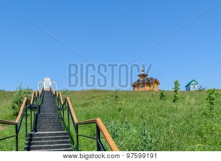 Metal Stairs With Railings Leading Up To The Place Of Prayer And A Wooden Chapel Near Small House