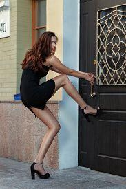 stock photo of indecent  - Girl put her foot in the door and wants to open it - JPG