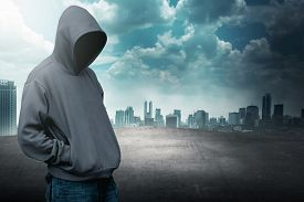foto of hoods  - Faceless man in hood on the rooftop with city background - JPG
