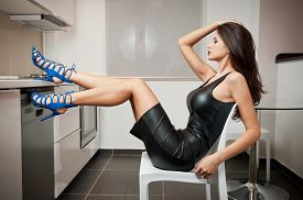 pic of tight dress  - Perfect body woman in short tight fit leather dress and blue shoes posing relaxed in a modern kitchen - JPG
