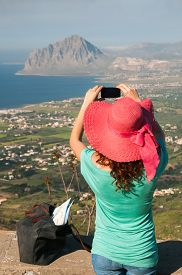 foto of promontory  - Tourist girl with a pink hat taking a photo of the promontory of Mount Cofano with her smart phone from an elevated viewpoint near Erice Sicily - JPG