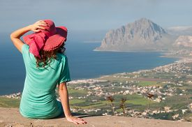 image of promontory  - Tourist girl with a pink hat looking at the promontory of Mount Cofano from an elevated viewpoint near Erice Sicily - JPG