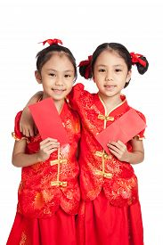 foto of identical twin girls  - Asian twins girls in chinese cheongsam dress with red envelopes isolated on white background - JPG