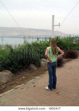 Young Woman/Tourist Standing In A Park Looking At The Sea