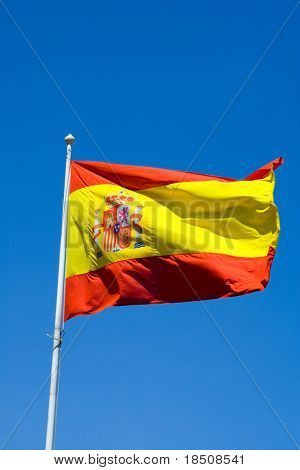 Flag of Spain flying in the wind against a blue sky