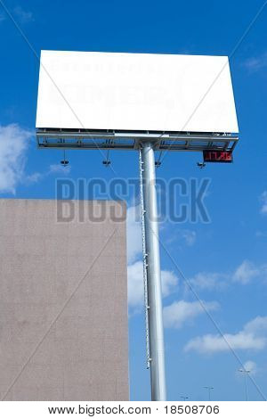 Blank billboard with digital clock against blue sky during rush hour