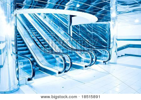 blue footsteps of moving escalator in office center