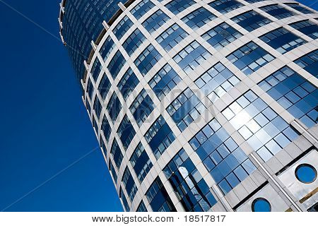 textured tower skyscraper with reflection of blue cloudless sky