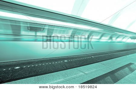 green moving train on underground platform