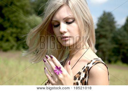 A pensativa menina com uma flor do campo