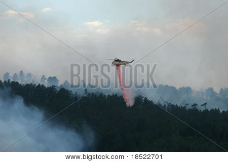 Helicopter dropping retardant on a forest fire