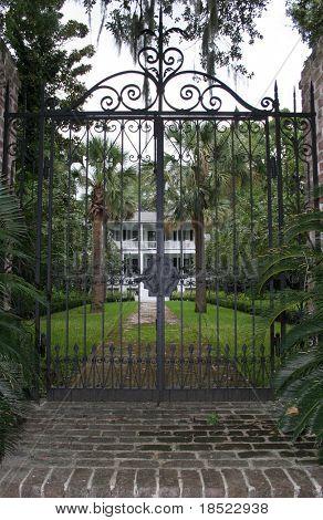 plantation home through a closed gate