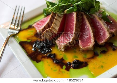 brazed raw tuna garnished with spinach over passionfruit sauce
