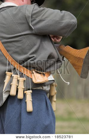man in period costume loading muzzle loading musket