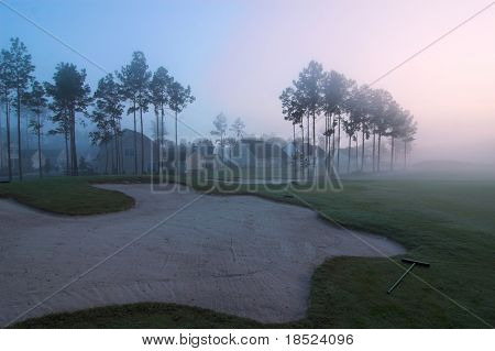 misty golf course sand trap with homes in background, predawn