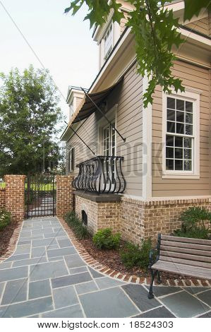 house with quaint courtyard with bench and slate patio