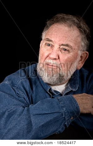 old man with look of anger or betrayal, isolated over black