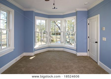 blue bedroom with lots of windows looking out onto pond