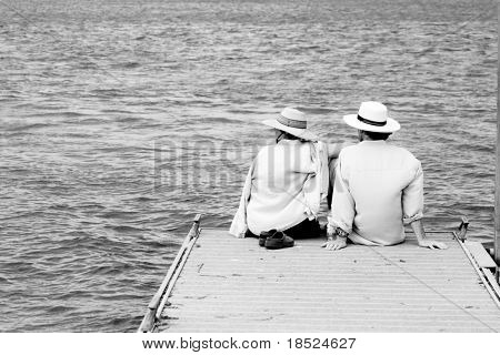 couple relaxing together on dock, black and white