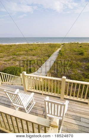 view of beach from deck with rocking chairs