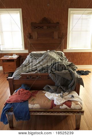 person sleeping late into morning on cluttered bed