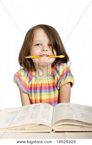 little girl biting pencil as she studies