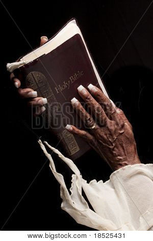 bible being held by wrinkled african american hands