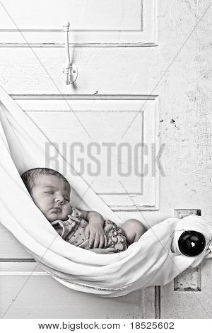 newborn baby sleeping in sling hung from door