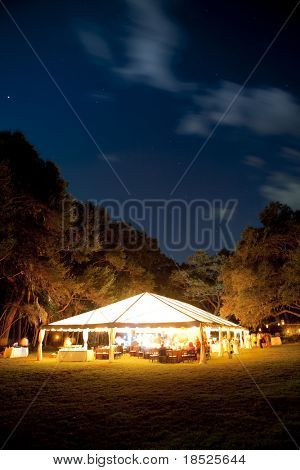large event tent lit up at night