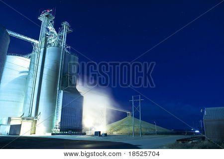 silo de grano y secadora en la noche con pila de grano