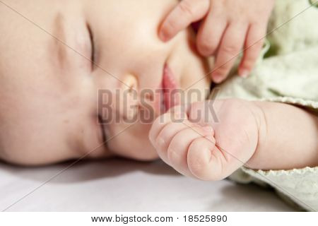 selective focus shot of baby hand with face of sleeping child in background