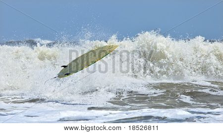 riderless surfboard in mid-air and breaking wave
