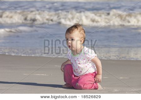 baby girl with surprised expression at the beach